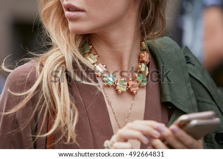 MILAN - SEPTEMBER 22: Woman with colorful necklace and two smartphone before Max Mara fashion show, Milan Fashion Week street style on September 22, 2016 in Milan.