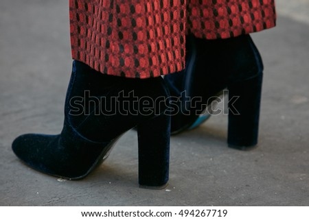 MILAN - SEPTEMBER 25: Woman with high heel boots in dark blue velvet before Salvatore Ferragamo fashion show, Milan Fashion Week street style on September 25, 2016 in Milan.