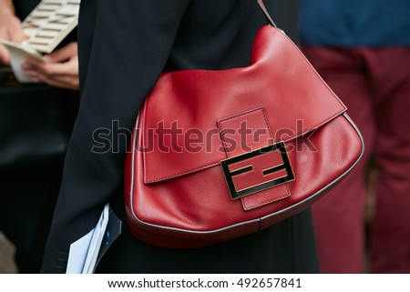 MILAN - SEPTEMBER 22: Woman with red leather Fendi bag before Fendi fashion show, Milan Fashion Week street style on September 22, 2016 in Milan.
