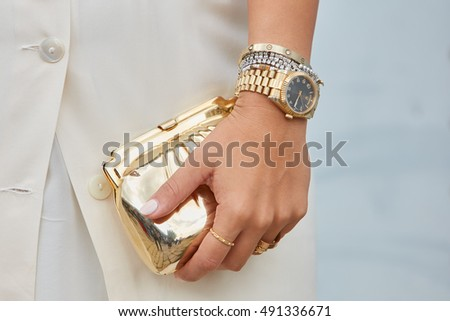 MILAN - SEPTEMBER 21: Woman with yellow gold Rolex Datejust and golden bag before Gucci fashion show, Milan Fashion Week street style on September 21, 2016 in Milan.