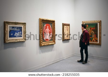 MILANO, ITALY - MARCH 27, 2010: Man looks at paintings galleries during MiArt, international exhibition of modern and contemporary art in Milano, Italy - stock photo
