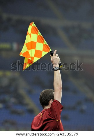 MILANO, ITALY-NOVEMBER 27, 2014: linesman holding flag at san siro stadium during the start of the UEFA cup soccer match FC Internazionale vsDnipro in Milan. - stock photo