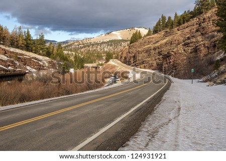 Mile one of a Montana frontage road promises to be interesting with an immediate warning for a 30 mph curve ahead and beautiful scenery - stock photo