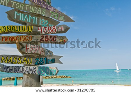 mileage signpost on key west florida beach, focus on signpost - stock photo
