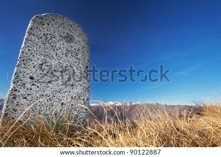 Milestone along an old road in the mountains - stock photo