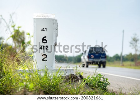 Milestone on the side of the road - stock photo