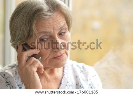 Miling senior woman calling on phone at home