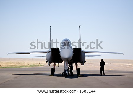 military aircraft - F-15 strike eagle on tarmac with pilot and technician - stock photo