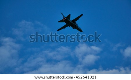 Military airplane flying in the sky.