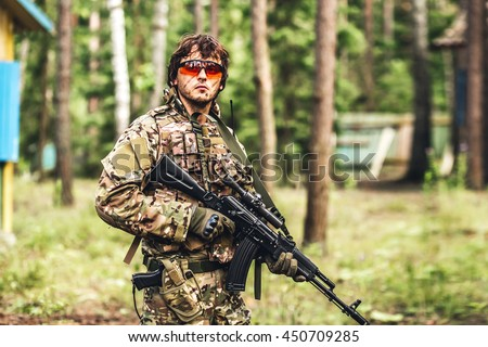 military. Armed man in a zone of armed conflictsoldier in uniform targeting with assault rifle outdoors - stock photo