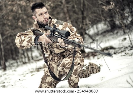 Military army trooper with gun and rifle in operation on battlefield - stock photo