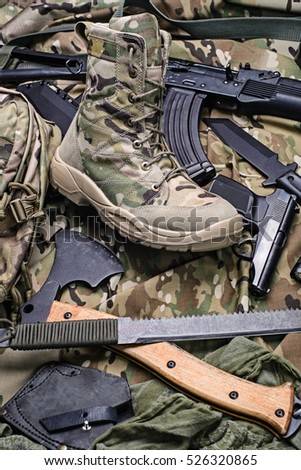 Military boot, an ax, pistol and rifle top view.Selective focus/One army boot and different weapon.Selective focus