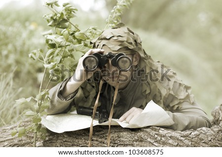 Military Camouflaged man in forest with black handgun and binocular - stock photo