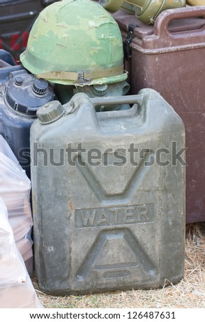 Military canister with helmet. - stock photo