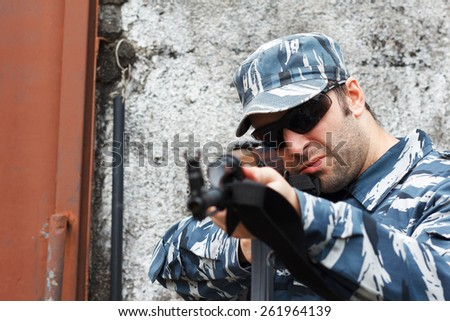Military caucasian man with black sunglasses in urban warfare aiming with rifle. Selective focus on face - stock photo