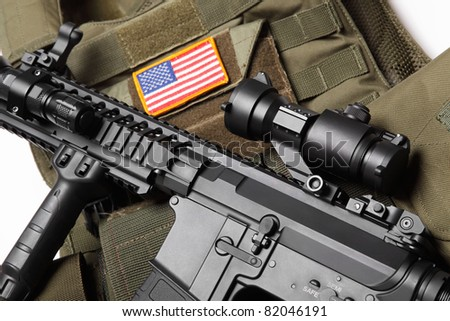 Military concept. Green tactical body armor with U.S. stripe flag and M4A1 assault rifle close-up. Studio shot. - stock photo