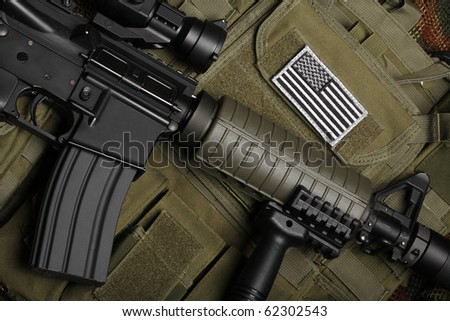 Military concept, still life. Tactical vest with U.S. battle flag and assault rifle with red-dot sight and tactical grip close-up. Studio shot. - stock photo