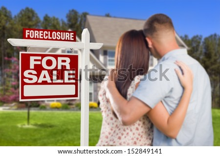 Military Couple in Front of House and Foreclosure For Sale Real Estate Sign. - stock photo