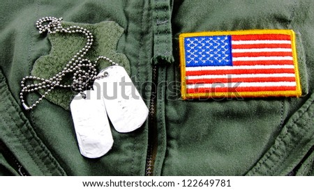 Military dog tags and American Flag patch on pilot flight suit - stock photo