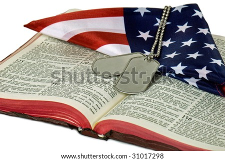 military dog tags and folded flag on bible - stock photo