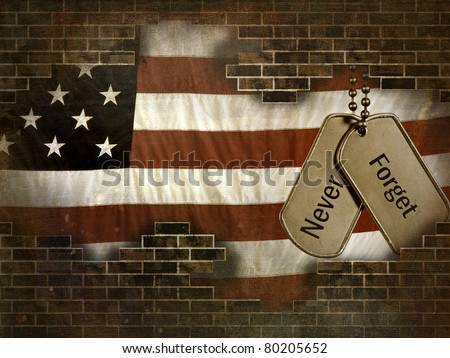 military dog tags on American flag behind a brick wall - stock photo