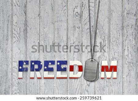military dog tags with freedom flag font on weathered gray barn wood - stock photo