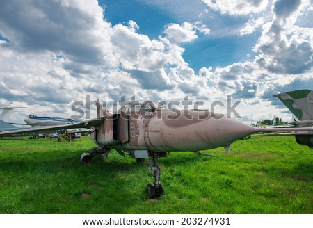 Military fighter plane on green grass - stock photo