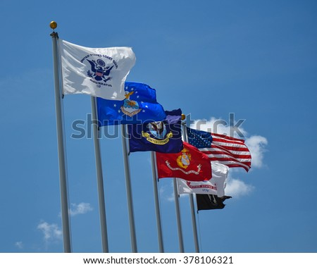 Military Flags Flying Proudly in a Clear Blue Sky - stock photo