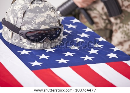 Military funeral - helmet on the american flag and soldier in the background - stock photo