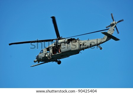 military helicopter flying overhead on a clear day - stock photo