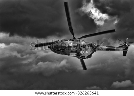 Military helicopter landing. Dramatic stormy sky. - stock photo
