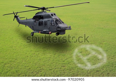 military helicopter landing on grass field - stock photo