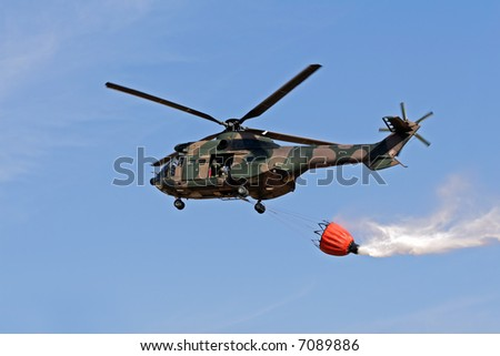 Military helicopter with a bucket filled with water to fight a forest fire - stock photo