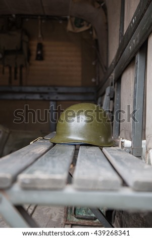 Military helmet on the bench of a military truck tank - stock photo