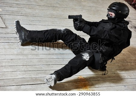 Military industry. Special forces or anti-terrorist police soldier,  private military contractor armed with pistol ready to attack lying on ground during clean-up operation, mission - stock photo