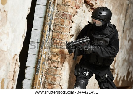 Military industry. Special forces or anti-terrorist police soldier, private military contractor armed with machine gun ready to attack during clean-up operation - stock photo