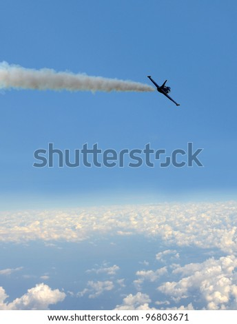 Military jet airplane flying above the clouds