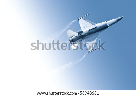 military jet flying through a gradient blue sky - stock photo