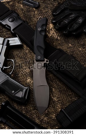 Military knife with rifle on black cloth. Top view: Army knife with gun. Marine corps knife represented on table. - stock photo
