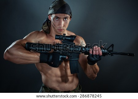 Military man. He is holding an automatic weapon. He has big muscles. - stock photo