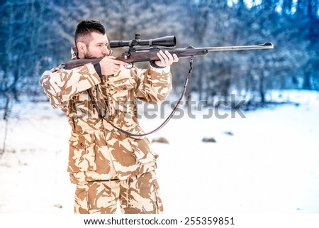Military man holding a sniper rifle and aiming at enemy on the battlefield - stock photo