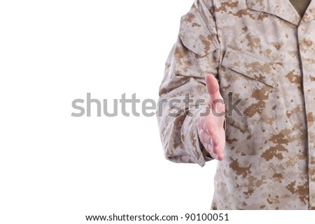 Military Man in Desert Fatigues Offers Handshake - stock photo