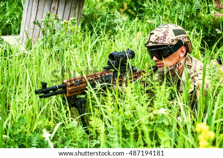 Military man sniper with automatic rifle with a telescopic sight lies in grass in forest. Airsoft