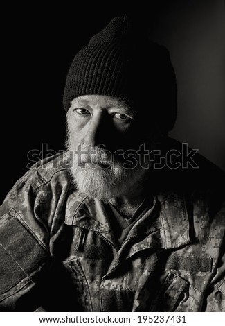 military man wearing camo jacket and knit cap staring into camera against a dark background - stock photo