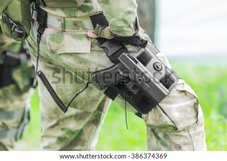 Military man with a gun on his leg - stock photo