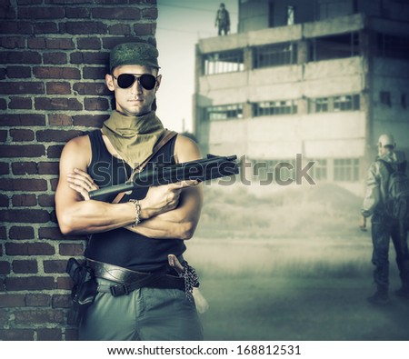 Military man with gun - automatic stay about brick wall in post apocalyptic world - stock photo