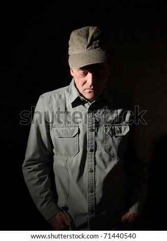 Military man with hands in pocket looking down - stock photo