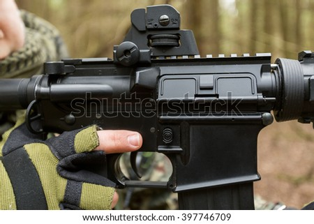 Military man with Rifle M16, hands holding automatic weapons, close-up - stock photo