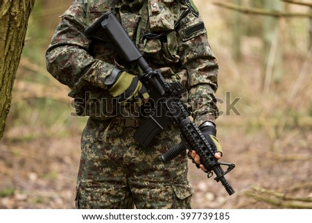 Military man with Rifle M16 outdoor forest, without a face - stock photo