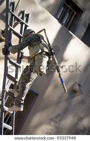 Military marksman going down a ladder with a silenced rifle